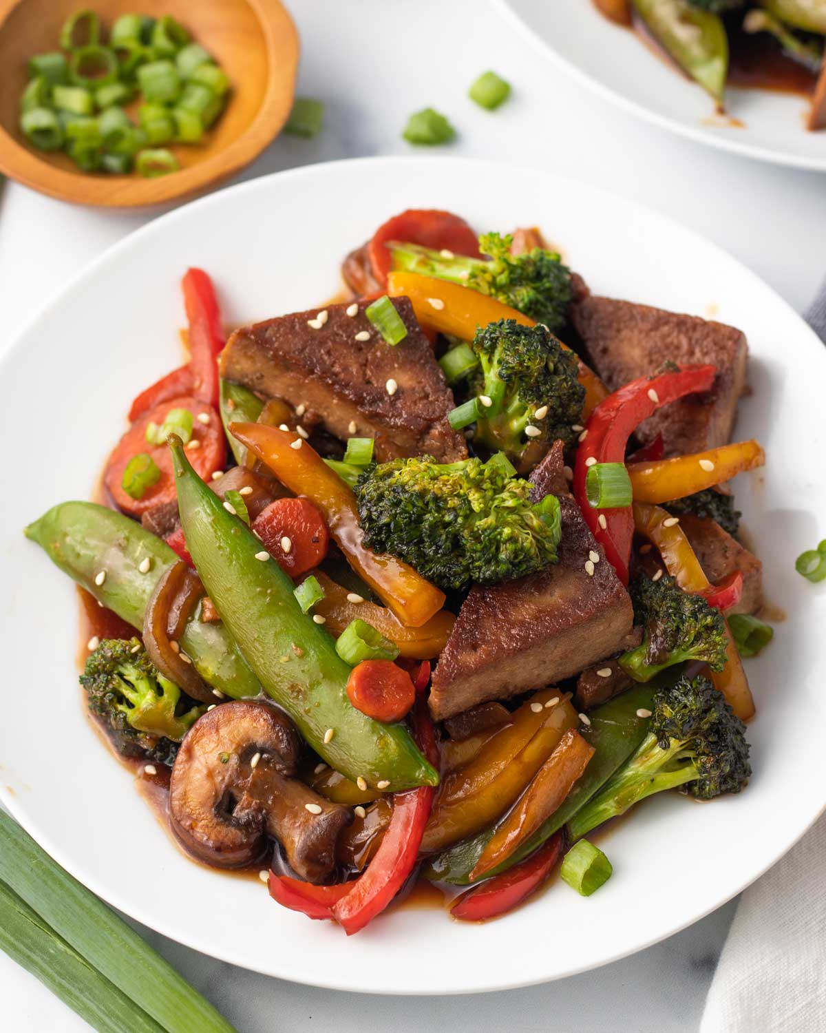 vegan tofu stir fry with colorful vegetables and sesame seeds on a white plate