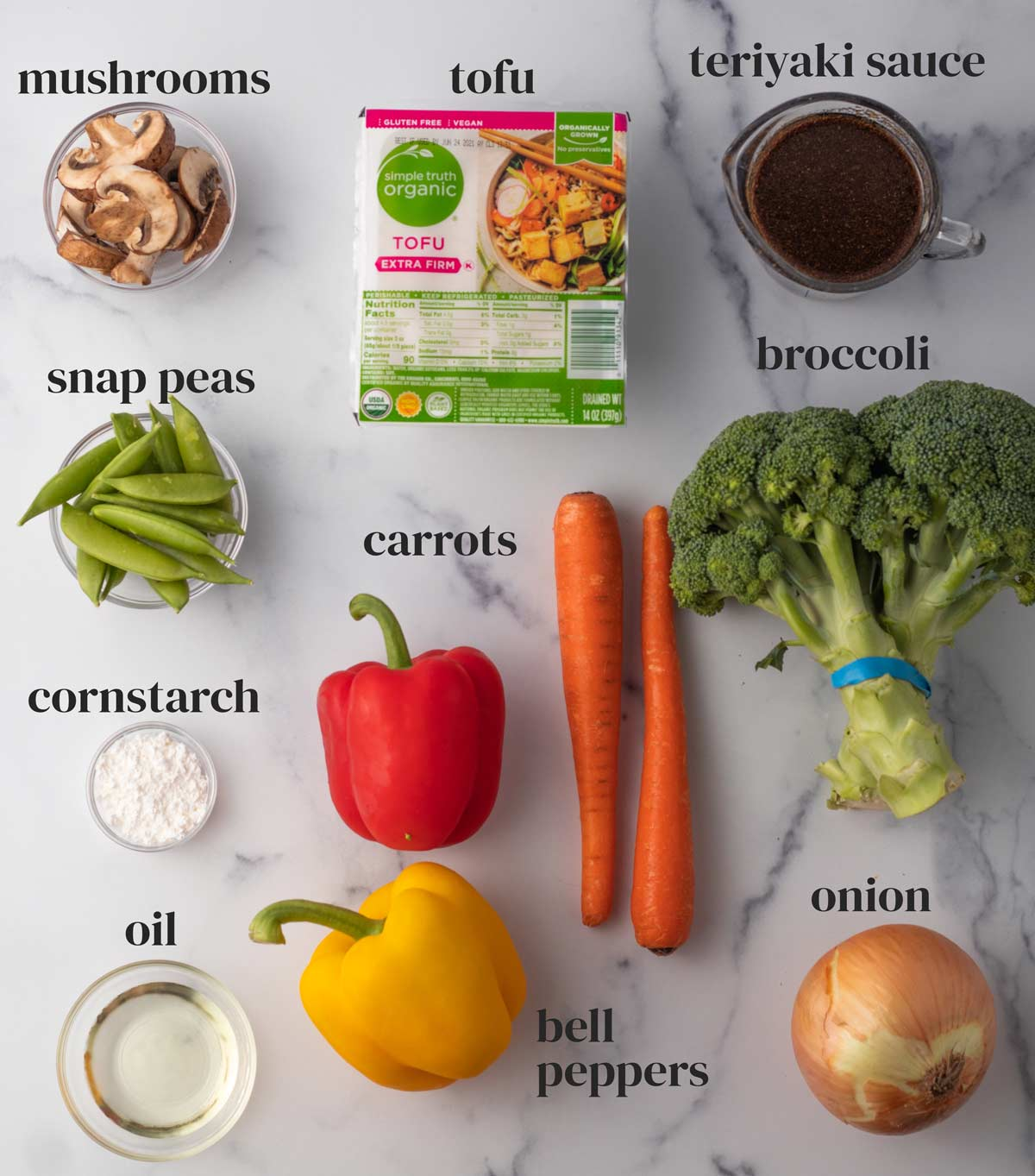 overhead of all ingredients to make teriyaki tofu stir fry with extra-firm tofu, broccoli, carrots, oil, peas, mushrooms and more vegetables
