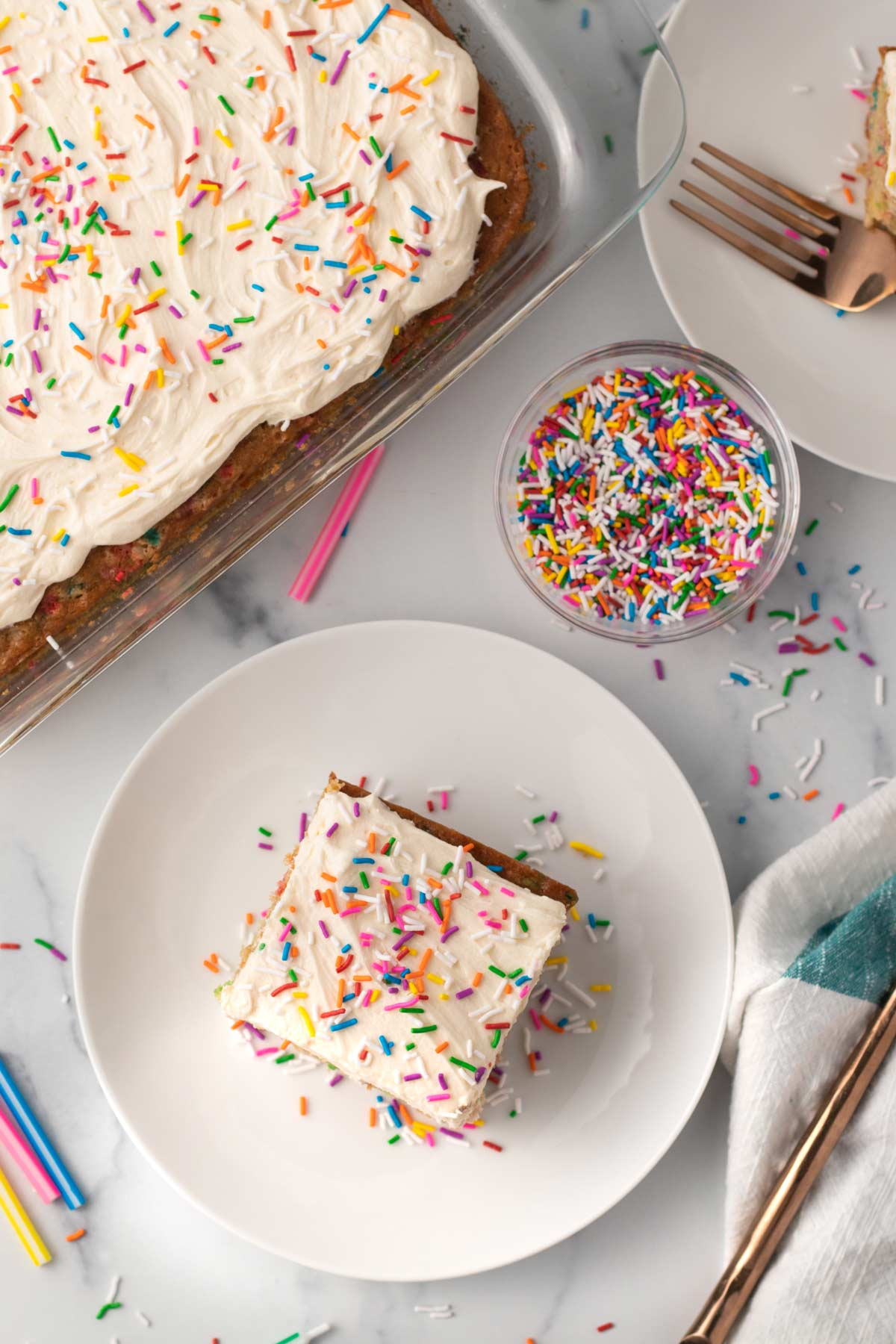 overhead of a plate with vegan funfetti cake and rainbow sprinkles
