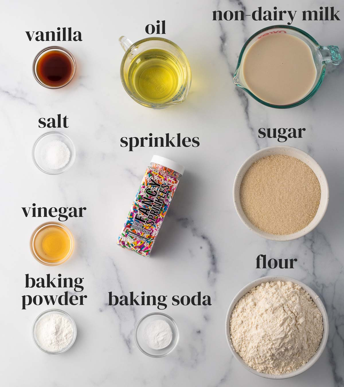 ingredients for vegan vanilla cake with rainbow sprinkles on a marble countertop
