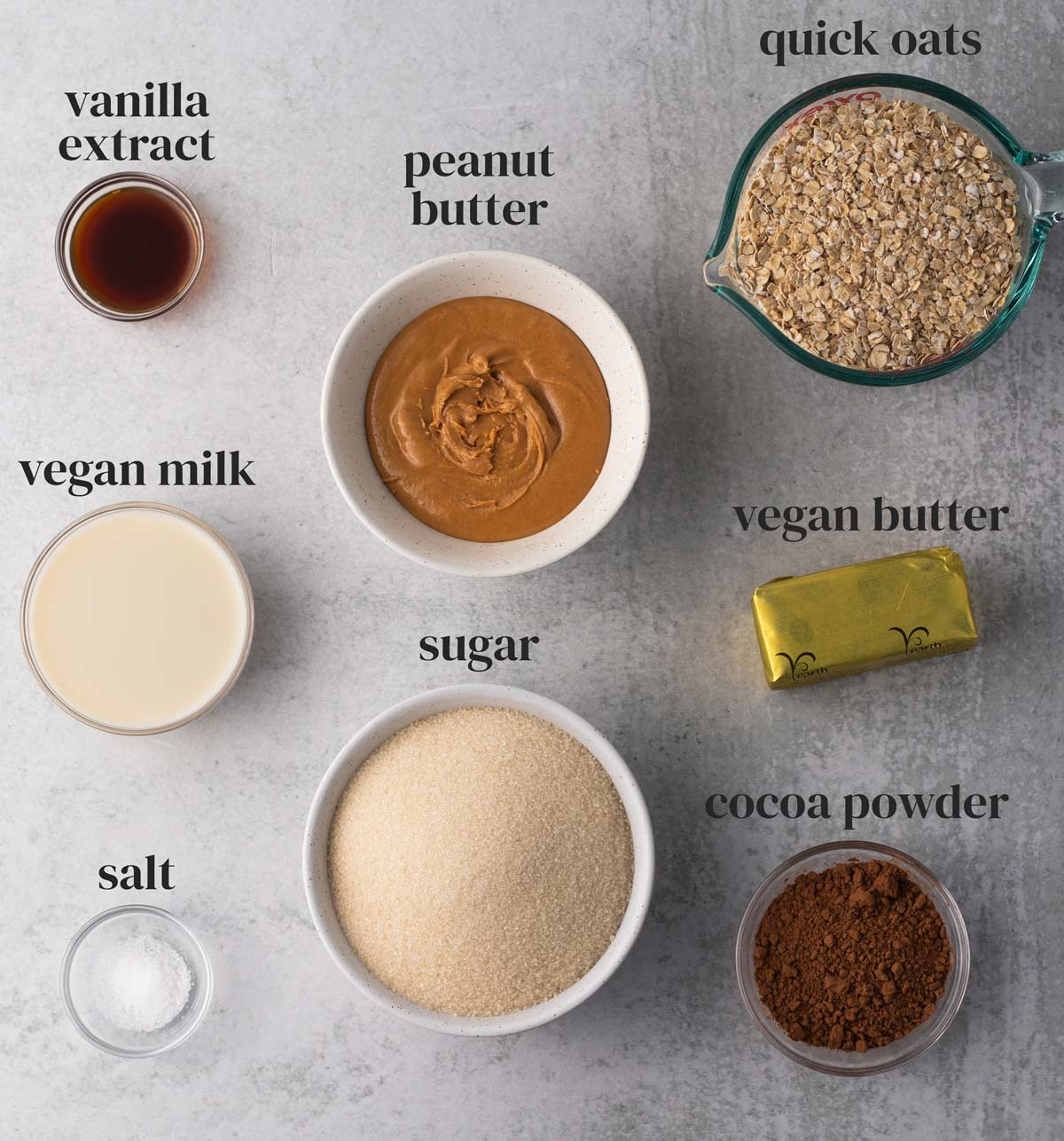ingredients for no-bake vegan cookies with oats, peanut butter, vanilla, sugar, chocolate, and salt