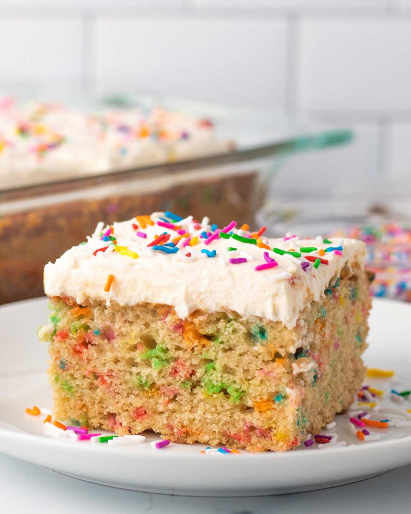 slice of vegan funfetti cake with vanilla frosting and colorful sprinkles