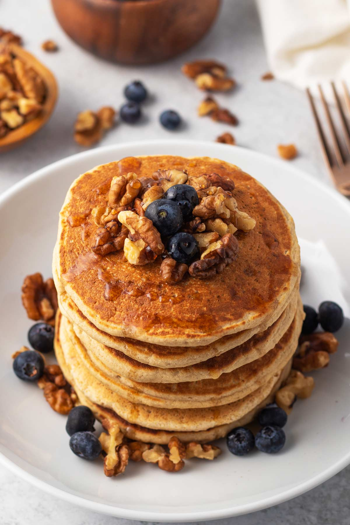 stack of gluten-free pancakes with blueberries walnuts and maple syrup on top.