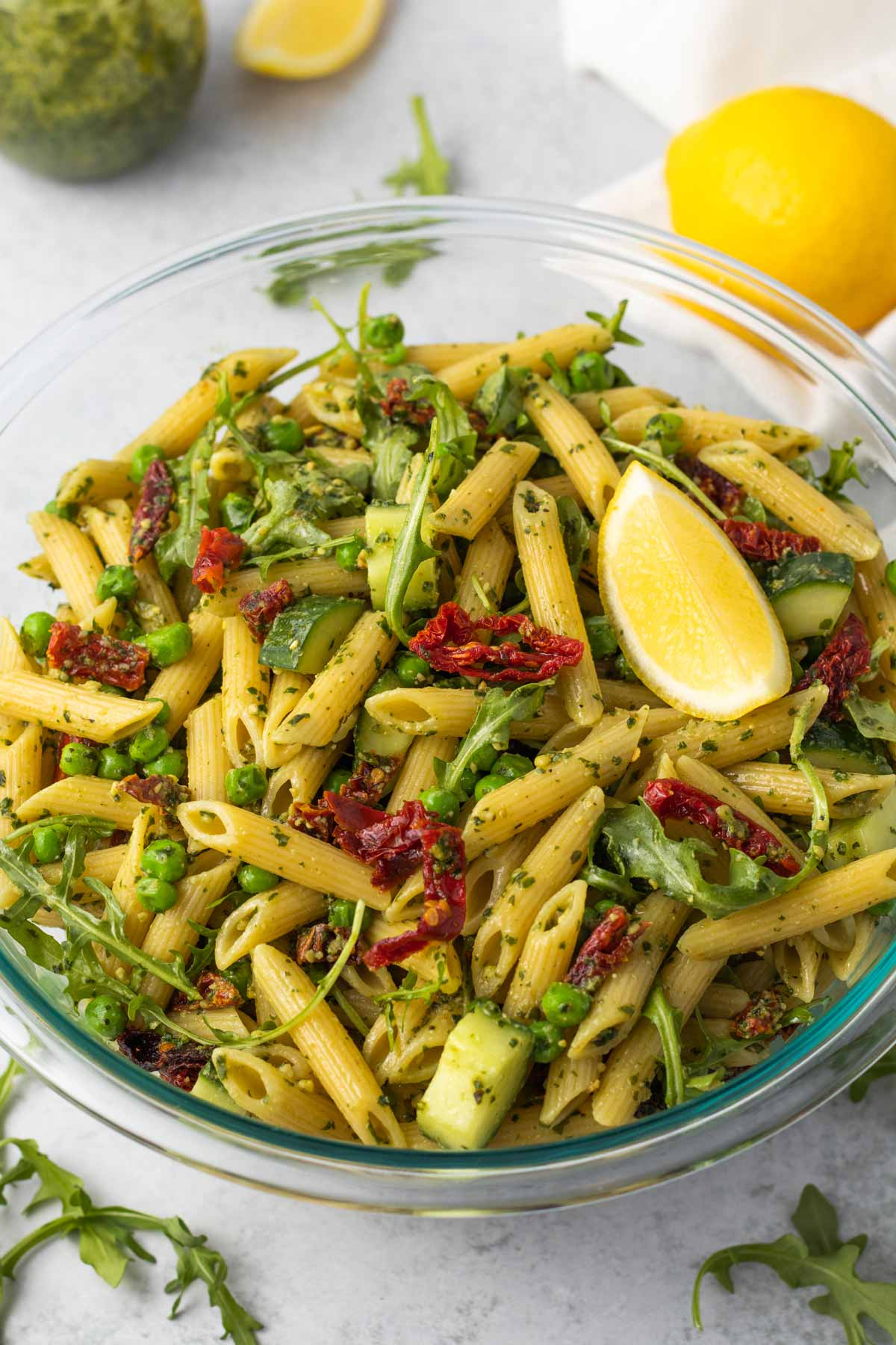Large bowl of pesto pasta salad, garnished with a lemon slice.