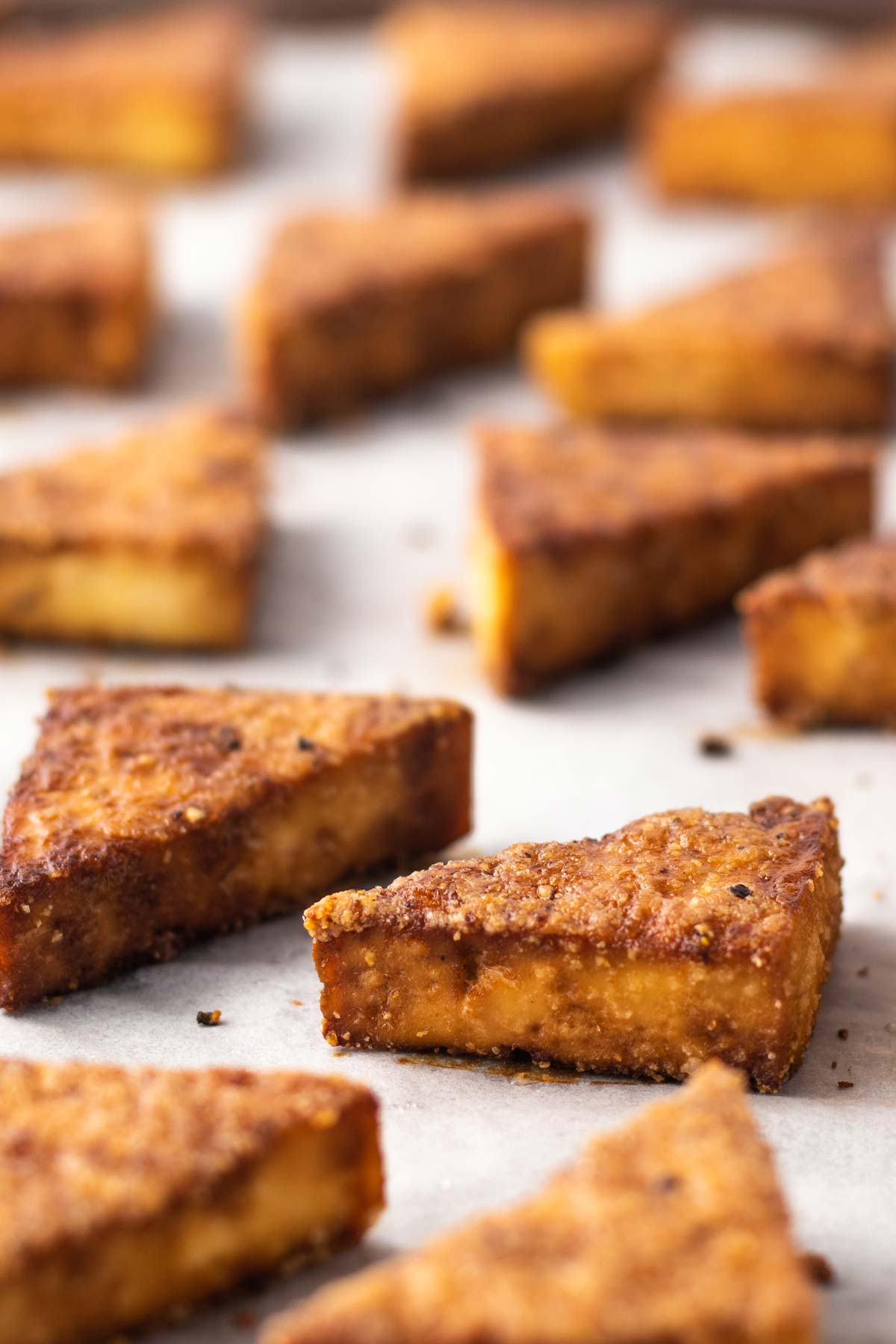cubes of baked tofu with soy sauce on a baking sheet