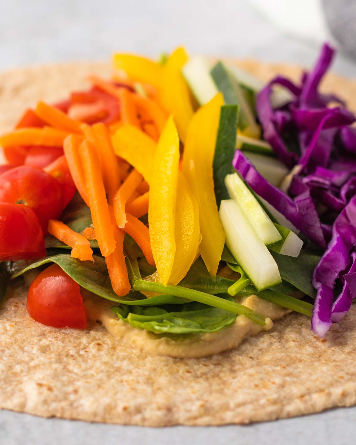 a wrap topped with hummus, carrots, peppers and other vegetables