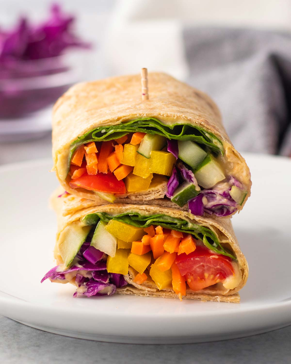 two hummus wraps with colorful vegetables stacked on top of each other on a white plate.