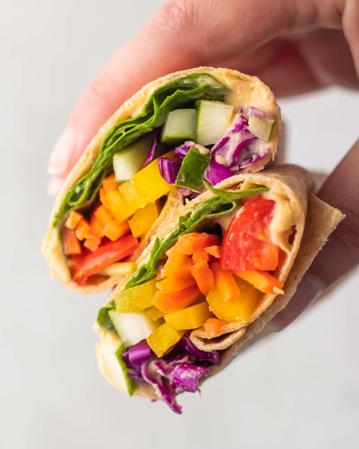 hand holding a hummus wrap with colorful raw vegetables.