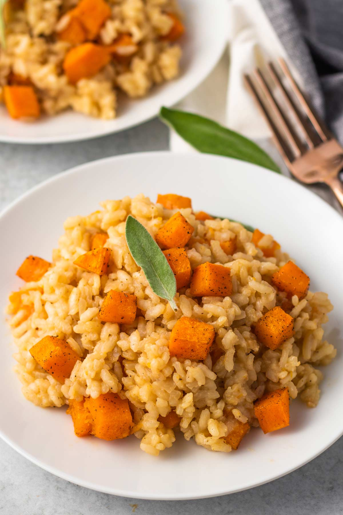 bowl of risotto with roasted butternut squash and a sage leaf on top.