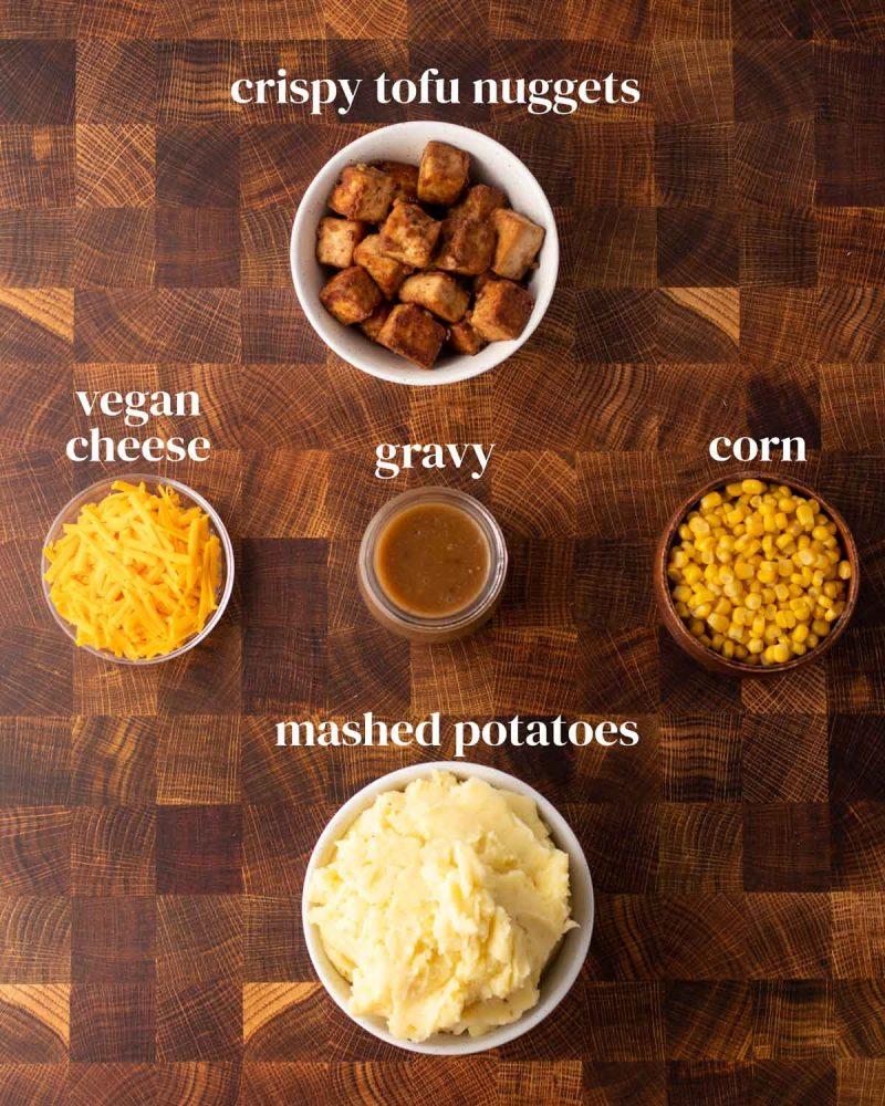 ingredients for kfc tofu bowl with corn, gravy, crispy tofu, cheese, and mashed potatoes