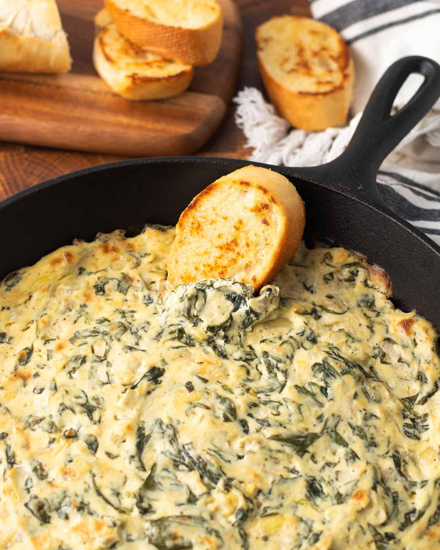 Vegan spinach artichoke dip in a cast iron pan.