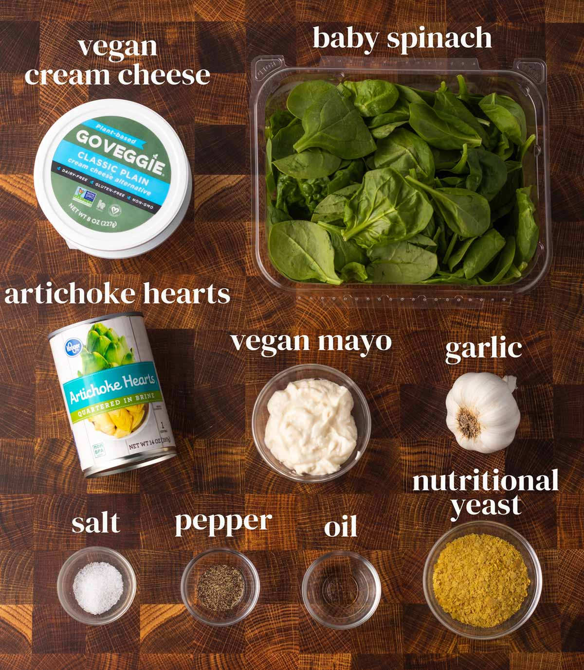 Ingredients laid out on a surface (dairy-free cream cheese, spinach, artichoke hearts, mayo, garlic, and seasonings.)