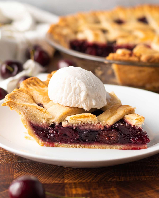 slice of vegan cherry pie with a scoop of vanilla ice cream