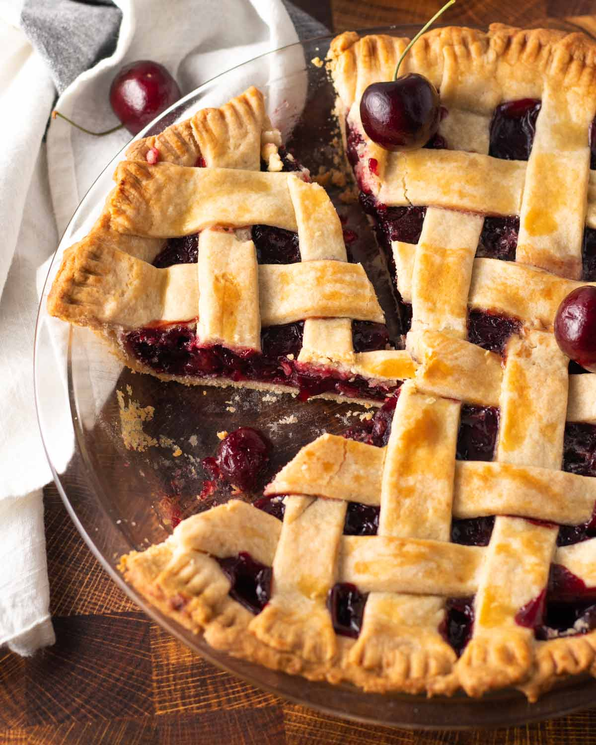 cherry pie in a pie plate with a slice removed