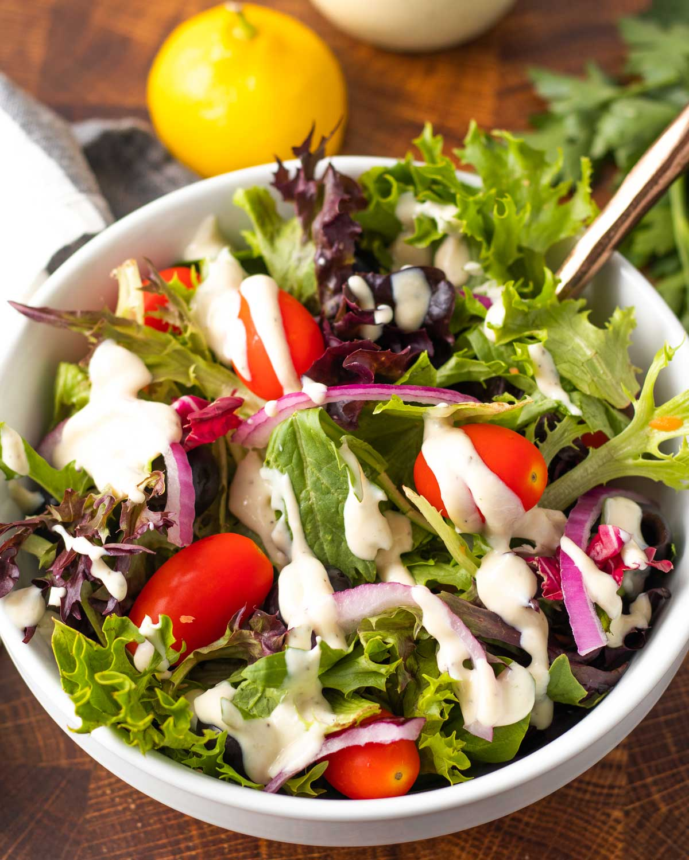 green salad with creamy italian dressing on top