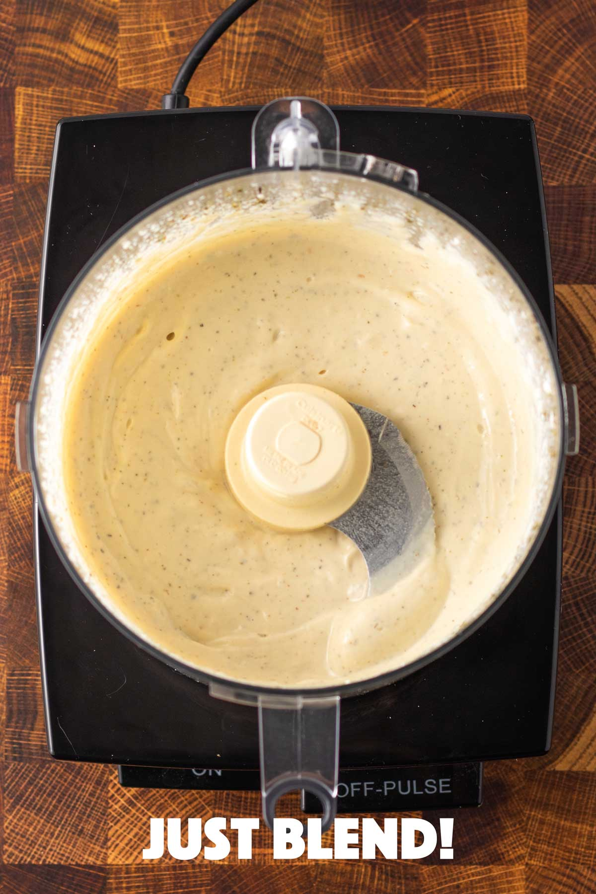 overhead of a food processor with creamy tofu-based dressing inside