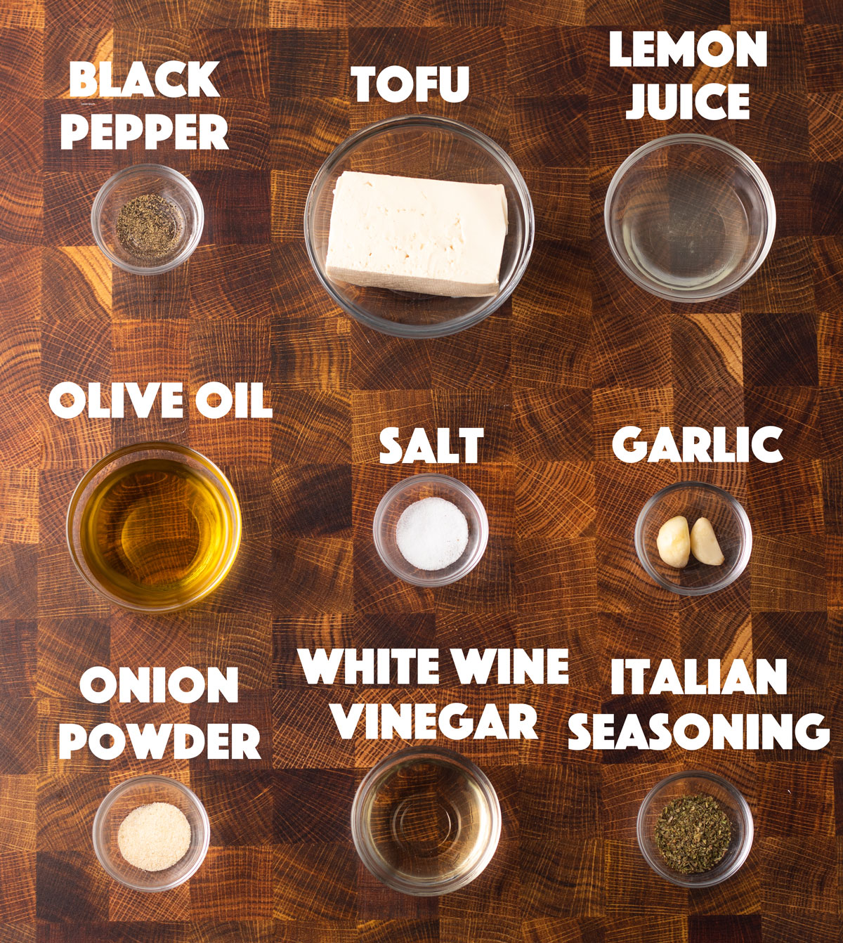 ingredients on a wooden board with tofu, lemon, salt, pepper, herbs and garlic
