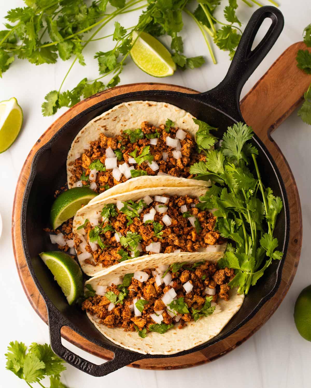 three tacos with tofu, white onion, and cilantro