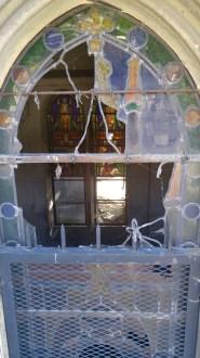 View of a tomb through a broken stain glass window (Cimetière du Père-Lachaise)