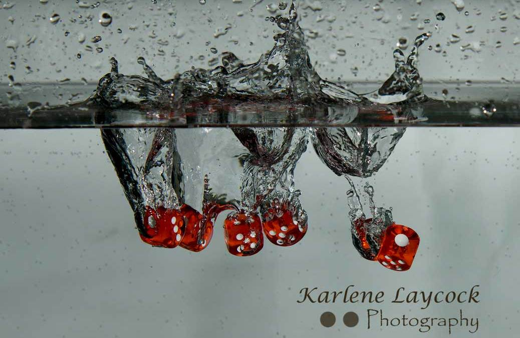 Red Dice falling into water on grey series 4