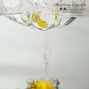 Lemon falling into water on grey 1