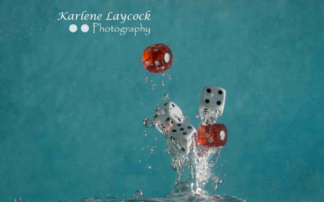 Red Dice falling into water on blue series 3