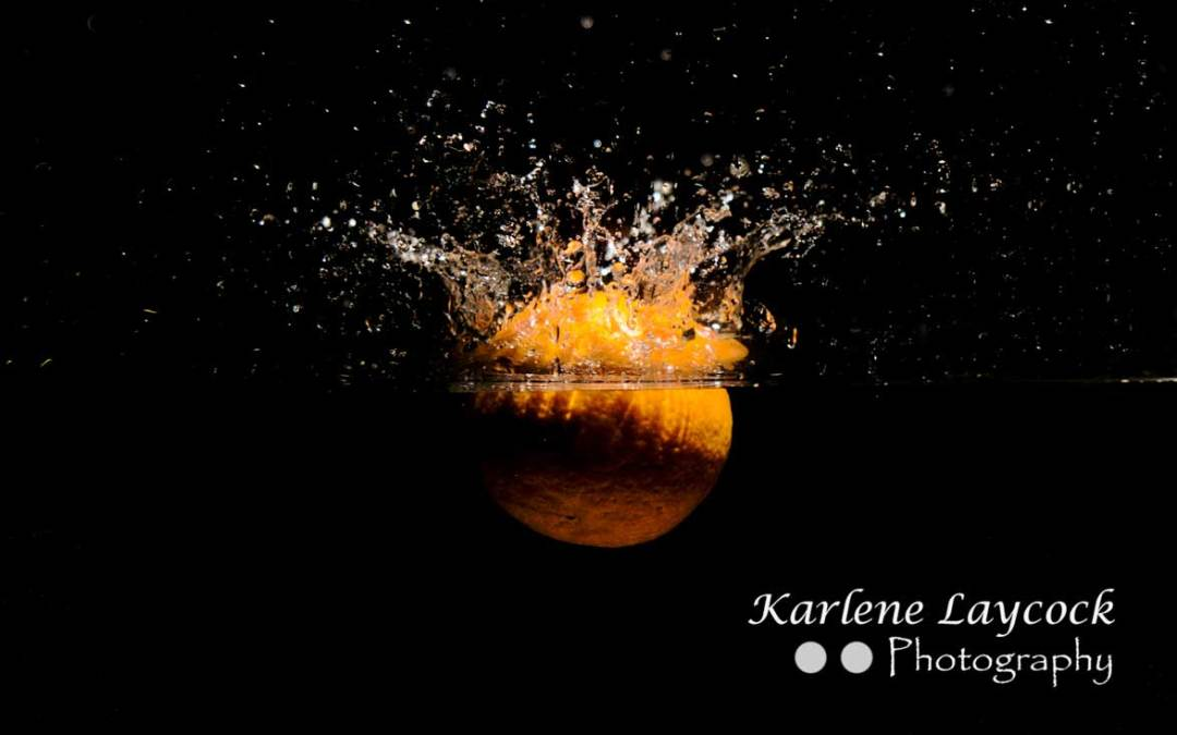 Orange splashing into water on black background 1