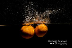 2 Orange dropping into water on black background 2