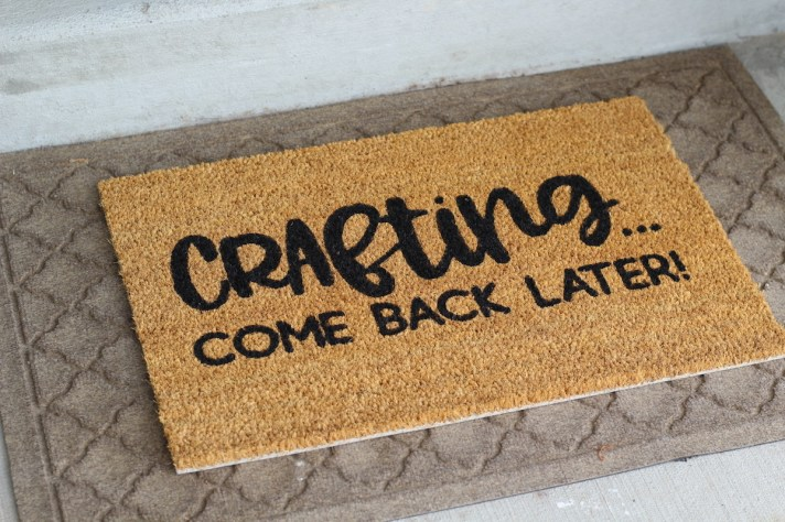 A handmade doormat with text 'Crafting come back later' made by Karleyhall.com