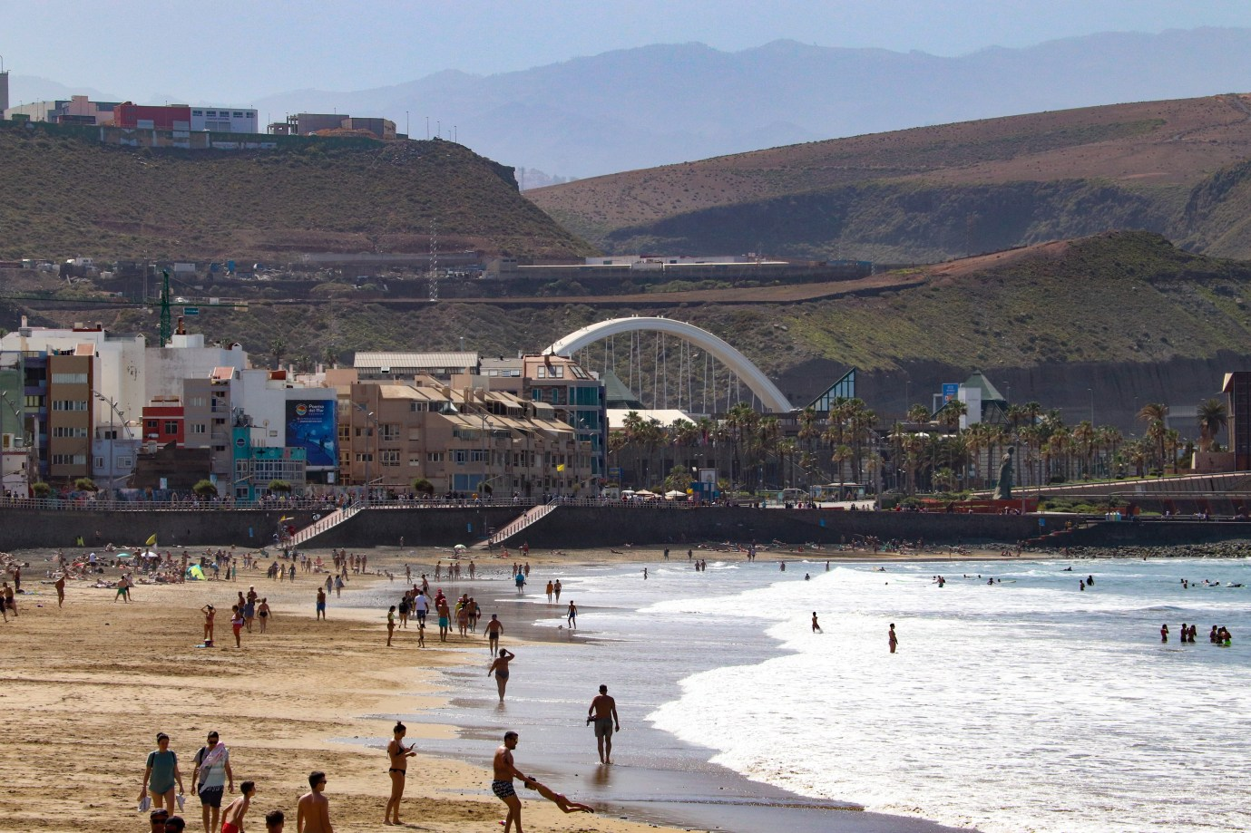 A view of the Playa de Las Canteras with the mountains of Gran Canaria visible in the distance.