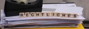 """Auf diesem Bild stehen die Buchstaben auf Akten und Papieren. Sie formen den Schriftzug """"Rechtliches""""."""