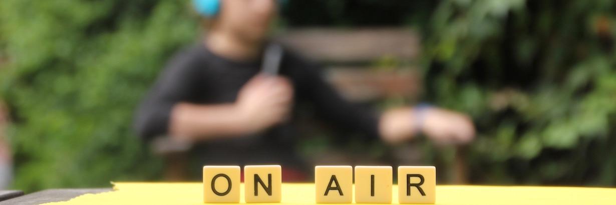 """Auf diesem Bild sagen die Buchstaben """"On Air"""". Im Hintergrund ist nur verschwommen eine Person mit Kopfhörern und Mikrophon erkennbar."""