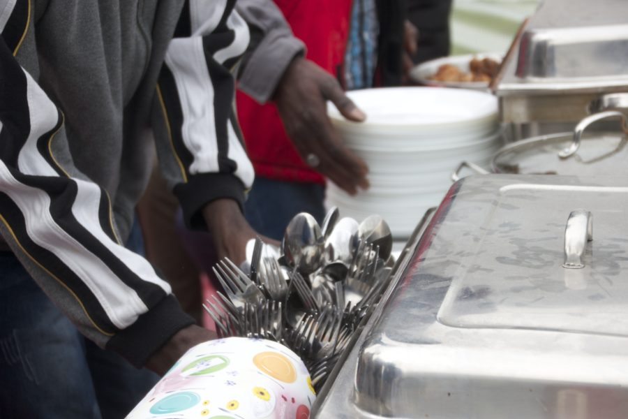 """Hier sind Geflüchtete aus Gambia bei einem Event in Heidelberg zu sehen. Sie haben als Projekt """"Sweet Home"""" gekocht und richten gerade die Teller für das Essen."""