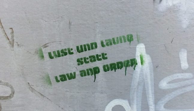 """Hier ist ein Stencil auf einer Wand in Passau zu sehen. Der Text lautet """"Lust und Laune statt aw and Order"""""""