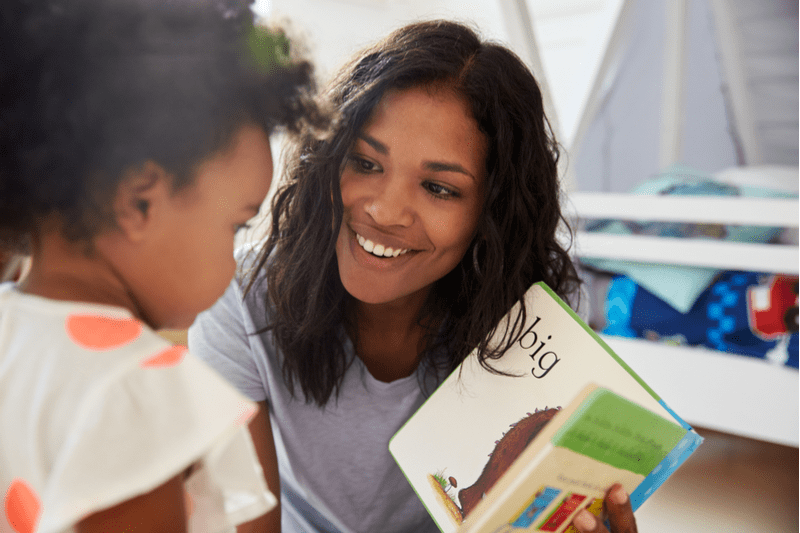 Black mother reads book to two year-old girl
