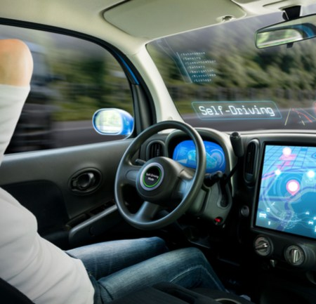 Driver of autonomous car relaxes with hands behind heads while viewing 360-degree view on screen