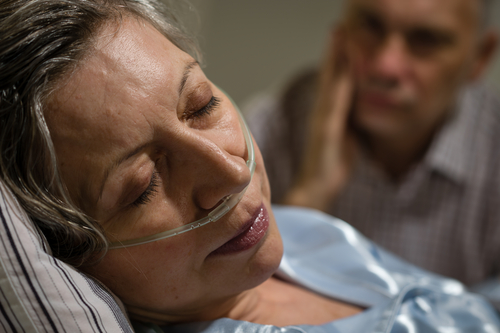 Worried husband by bedside of ailing unconscious wife with nasal canula