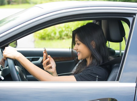 teenager looks at phone screen while behind the wheel of a car