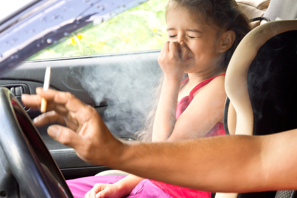 Child in car holds nose as parent smokes