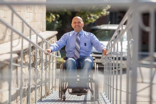older man rides access ramp in wheelchair