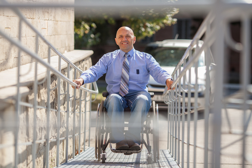 older man rides access ramp in wheelchair