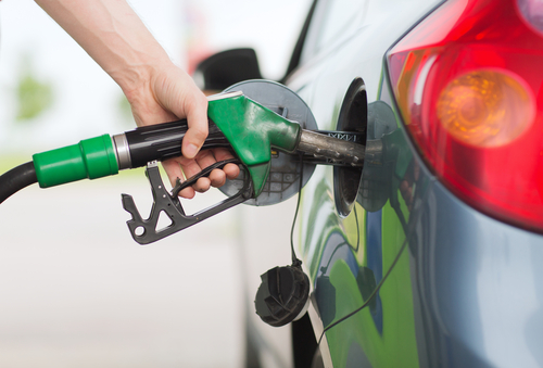 man's hand filling gas tank of car