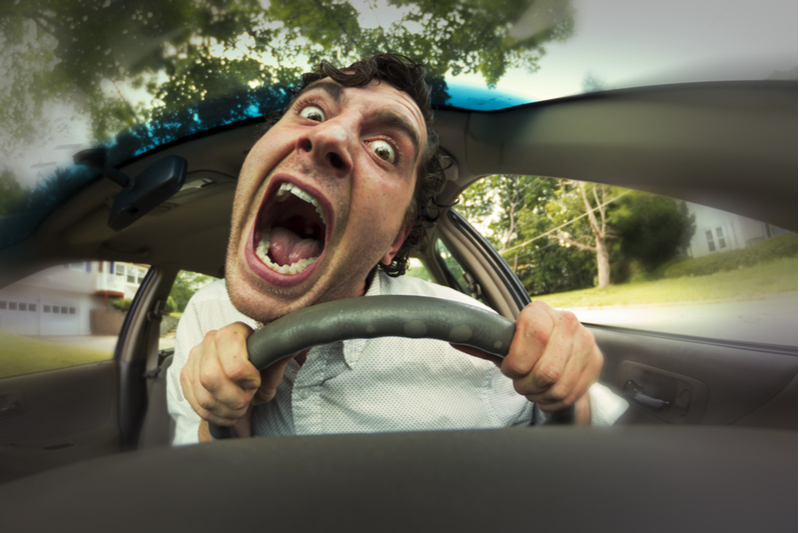 man screaming behind the wheel