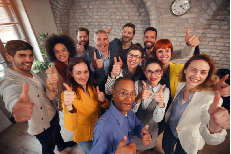 a happy team of employees giving thumbs up