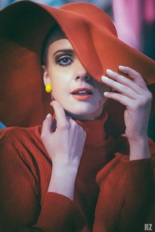 dolcevita rosso e cappello in panno falda larga con orecchini gialli