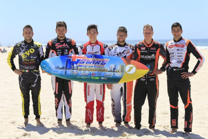 Six of the international drivers with the Winner's Surfboard trophy on the beach at Surfers Paradise