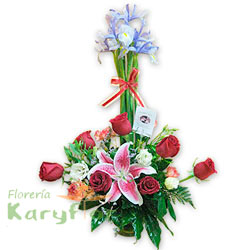 Lindo arreglo floral elaborado en base de cerámica, contiene 7 rosas importadas. Iris azul, variedad de flores y fino follaje. Incluye tarjeta de dedicatoria y lazo en organza Pueden adicionarles chocolates y peluches ingresando a la opción REGALOS en la parte superior de la Pág. web