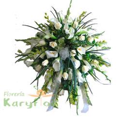 Elaborado en tripode de fierro con rosas importadas, calas blancas, gladiolos, fino follaje y lazo en horganza. Incluye tarjeta impresa con dedicatoria de condolencias.