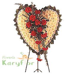 Corona corazón decorado con pompos, claveles importados, fino follaje en trípode especial. Incluye tarjeta impresa de defunción.