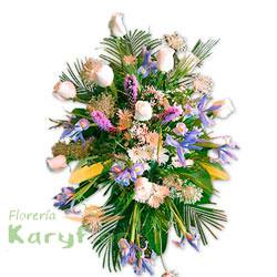 Manto con rosas importadas, fino follaje y variedad de flores en tripode de fierro. Incluye tarjeta impresa de condolencia. Se puede elaborar en distintos colores de rosa previa coordinacion.